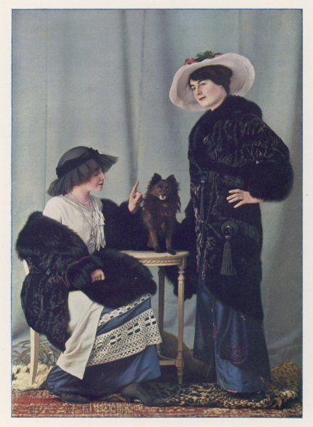 Two women with one 'live' furry friend. Tunic dress with crochet trim, black gauze hat, black fur muff; unspecifed black fur coat ornamented with large oriental style tassels
