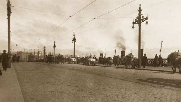 A view of carriages and pedestrians crossing the Galata Bridge in Constantinople, avoiding the electric trams