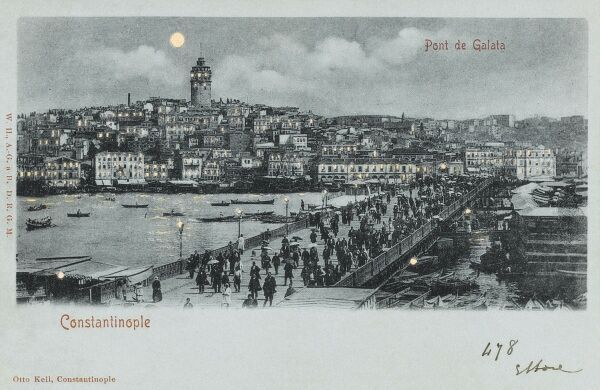 A 'Hold-to-light' postcard of the Galata Bridge in Constantinople with the Galata Tower in background at night