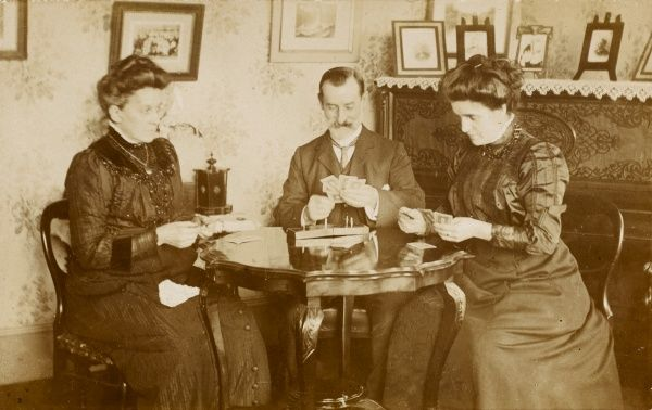 A man and two women play a game of bezique around a polished wood table in a comfortable drawing room
