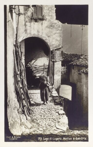Backstreet in Gandria on the shore of Lake Lugano, Switzerland. A woman walks up a steep cobbled passageway with a wicker basket on her back, past a large wood store. The lake itself can be seen through the opening on the lower right-hand side of the scene