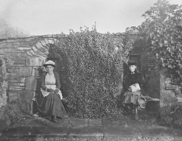 Two young ladies sit in old seats built into a garden wall in this atmospheric photograph