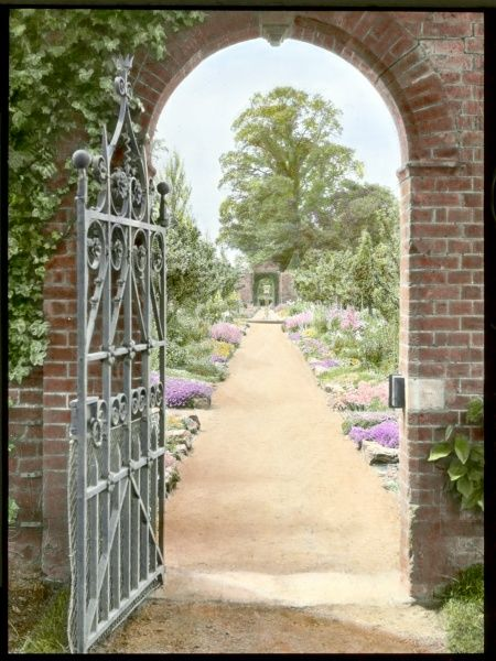 View of the gardens at Aldenham House, near Borehamwood, Hertfordshire, seen through an open gate in an archway