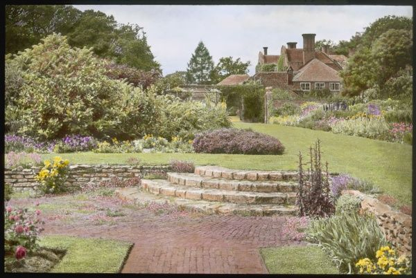 View of the gardens of Earlham Hall, near Norwich, Norfolk, showing steps, grass, flowers and shrubs, with the house in the background
