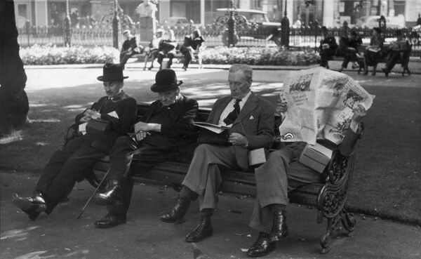 Men sitting in a London park carry their gas mask boxes with them in September 1939