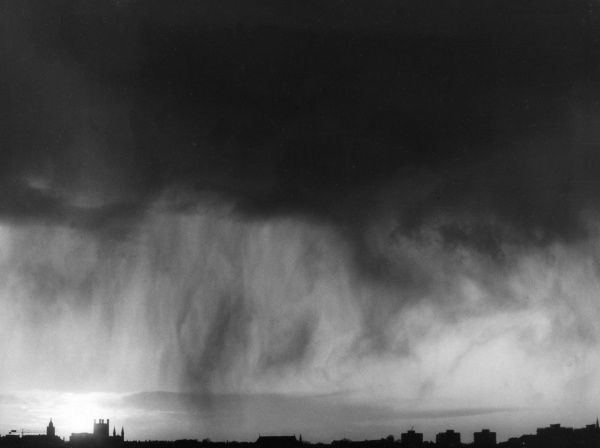 The Gathering Storm - ominous clouds and the start of a rain storm over an English cathedral city. Date: 1960s