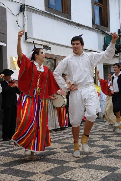 Two members of a folklore group from Gaula, seen here dancing in Funchal, the capital city of Madeira, with musicians playing in the background. The couple are wearing traditional costume, including black skull caps with points. The woman wears mostly red