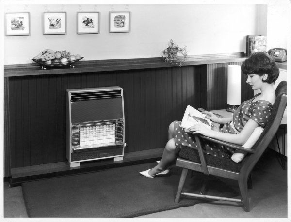 An attractive young housewife flips through a fashion magazine, warming her white stilettos by her 'Gay Glow' gas fire. Date: 1960s