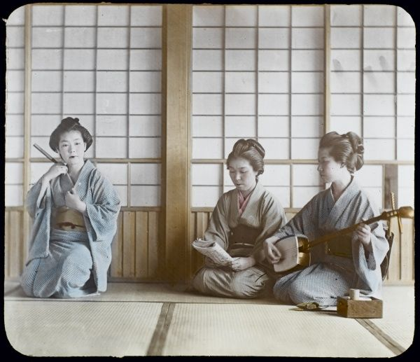 Three geisha, in informal kimono: one practises on her shamisen whilst another reads