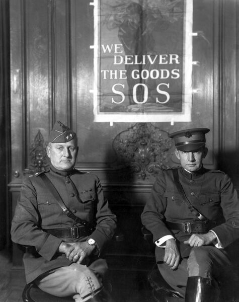 Major General James Guthrie Harbord (1866-1947), Chief of SOS (Services of Supply), and Brigadier General Charles Gates Dawes (1865-1951), both of them American army officers. Seen here in Paris with a poster behind them: We Deliver The Goods SOS