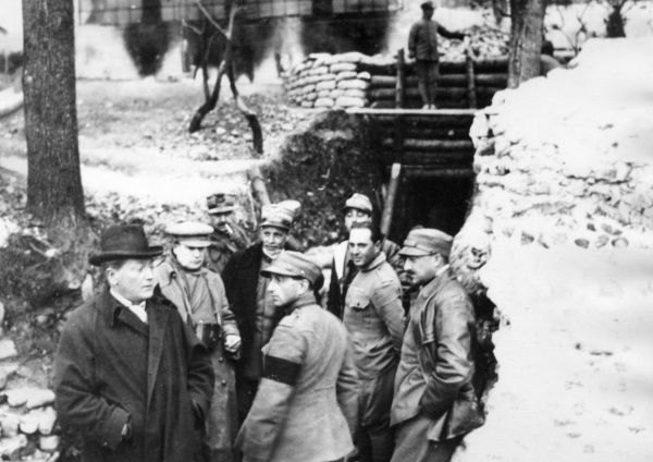 General Giuseppe (nickname Peppino) Garibaldi (1879-1950), in a trench with others, including an English or American journalist, during the First World War. He is at the centre of the group, wearing a general's cap and a dark overcoat. Date