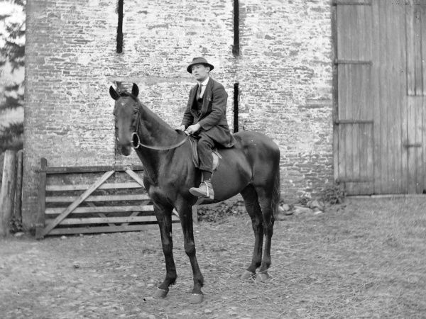 A gentleman riding a stallion near some stables, probably somewhere in Mid Wales