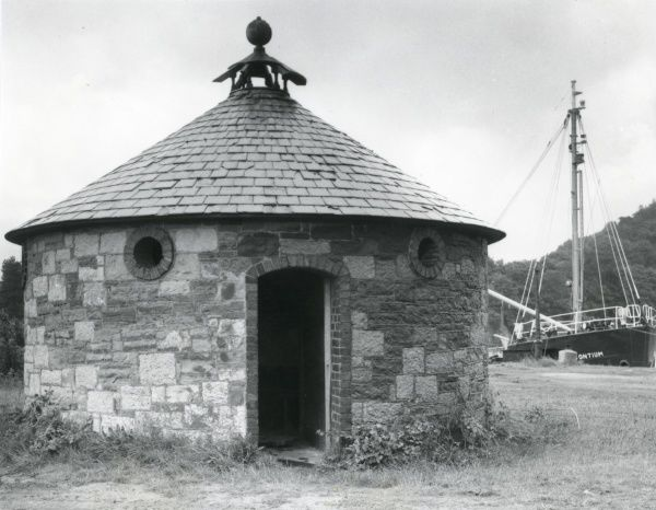 A circular gents toilet, built in 1850 with stone walls and a slate roof, somewhere in North Wales where the slate is quarried
