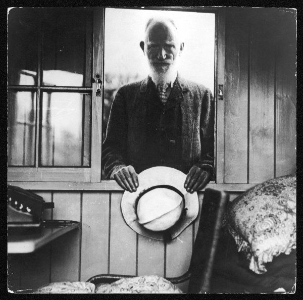 GEORGE BERNARD SHAW Irish writer standing looking in through an open window of the shed at the bottom of his garden where he used to write