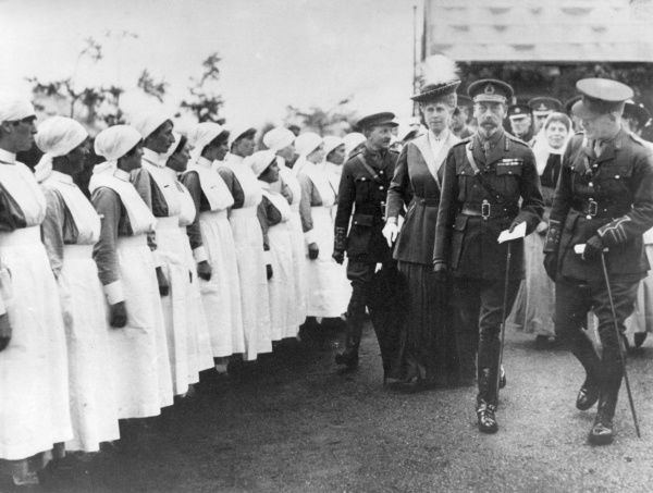 King George V and Queen Mary with others, visiting a hospital during the First World War. Nurses stand in line on the left. Date: circa 1916-1918