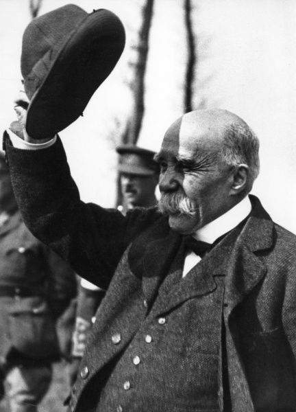 Georges Benjamin Clemenceau (1841-1929), French Prime Minister from 1906 to 1909, and again from 1917 to 1920. Seen here during the First World War, raising his hat, with soldiers in the background. Date: circa 1917