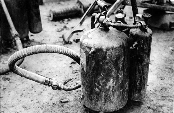 Photograph showing a captured German flame-thrower, displayed in a yard behind the French lines, 1916. This flame-thrower, or 'flammenwerfer', was captured during one of the battles of the Somme