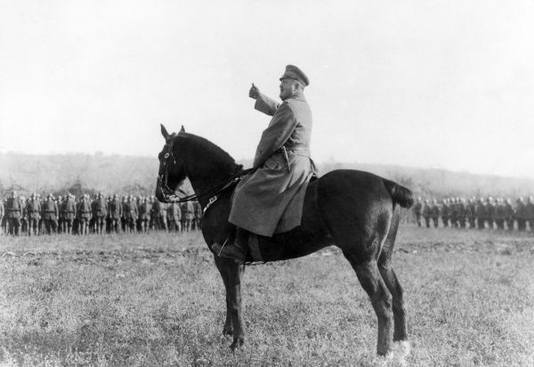 A German (or Austrian) General on horseback, speaking to troops, at Piave, Italy, during the First World War. Date: December 1917