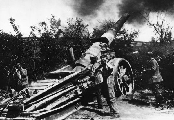 German gunners in action with a 17cm naval gun during the First World War. Two of them are covering their ears as protection from the blast. Date: 1914-1918