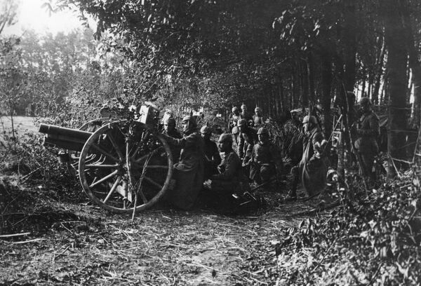 German gunners in a camouflaged position with a 77mm Model 1896 field gun ready to fire on the Western Front during the First World War. Date: 1914-1918