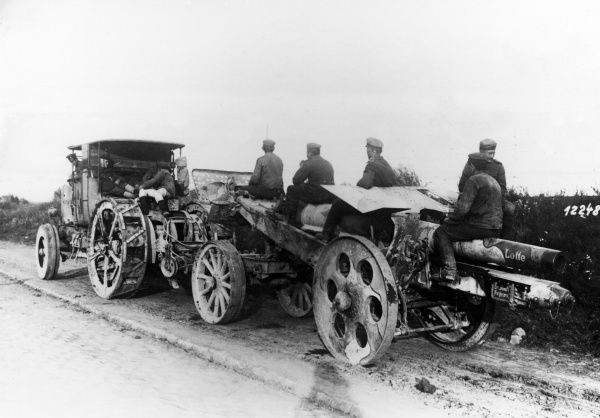 A German camouflage-painted howitzer, with several gunners, being transported by tractor along a road on the Western Front towards the end of the First World War. The name Lotte is painted on the barrel. Date: September 1918