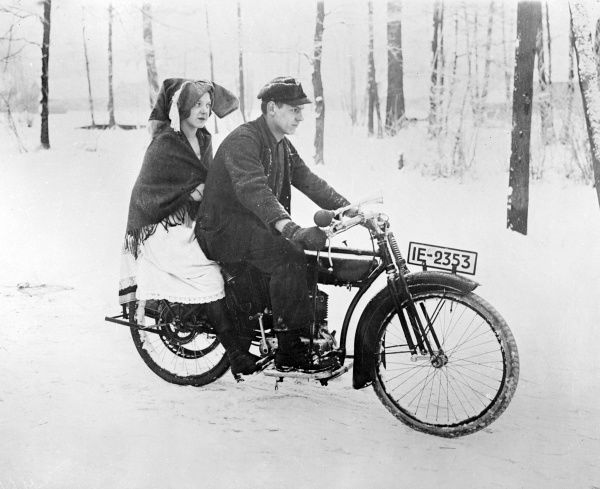 A German girl from Spreewald rides on the back of a motorcycle in rather impractical tradtional dress! Date: early 1930s