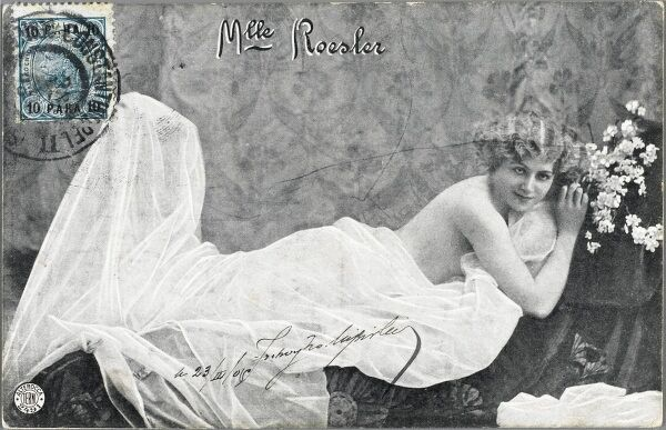 A German Music Hall entertainer, Mademoiselle Roesler, posing for a portrait photographer in an alluring position under a white sheet