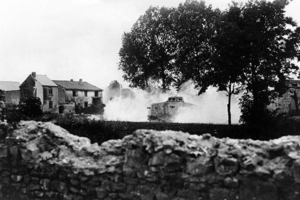 A German tank going into action outside a village on the Western Front during the First World War. Date: June 1918
