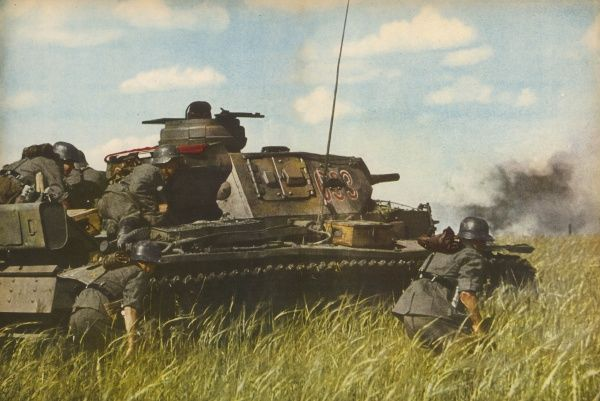 A German tank, accompanied by infantry, advances across the Russian steppes