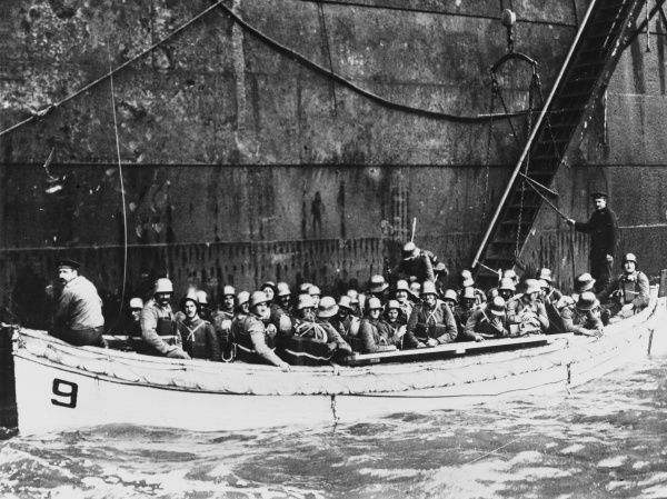German troops, wearing lifebelts, in a small boat having disembarked from the larger troopship alongside, prepare to make an amphibious landing on Oesel Island (Saaremaa, off the coast of modern day Estonia)