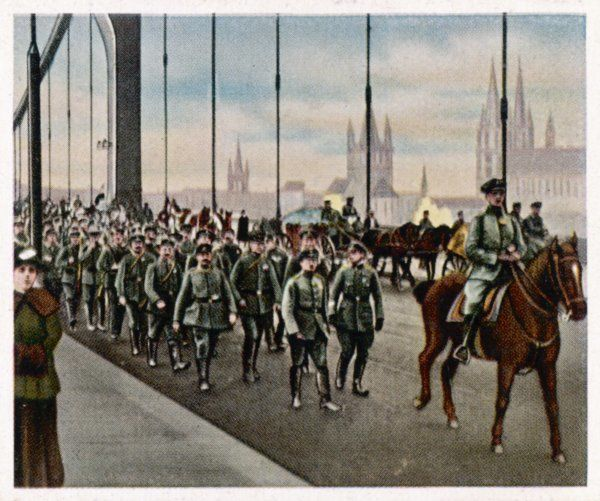 German troops march over a bridge on their way back home from the war