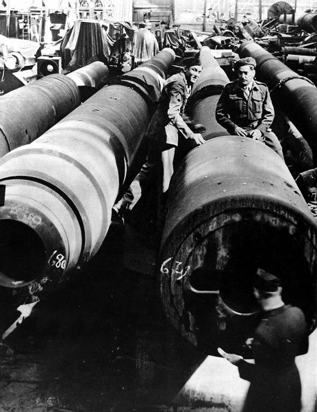 Photograph showing British and American soldiers examining some German gun barrels, each 28 yards long, captured in Essen, Germany, 1945. These barrels, 11-inchs in calibre, were designed for shelling an extremely distant target