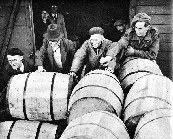 Photograph showing a group of German workers unloading barrels of powdered milk from a British truck, under the supervision of a British Soldier, Berlin, August 1945. At the end of the Second World War in Europe there were great shortages of food