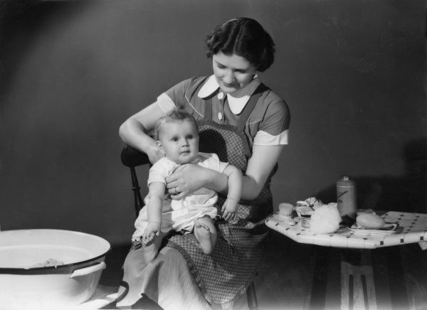 A mother gets her baby ready for his bath. Soap, talcum powder and cotton wool are ready on a table at her side