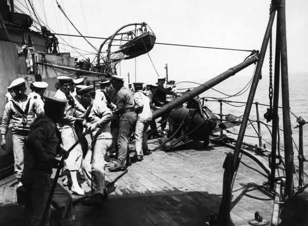 The crew of a ship getting out the paravanes on entering a minefield during the First World War. The paravane is towed underwater in order to detect the presence of mines, and has saved many ships from destruction. Date: 1914-1918