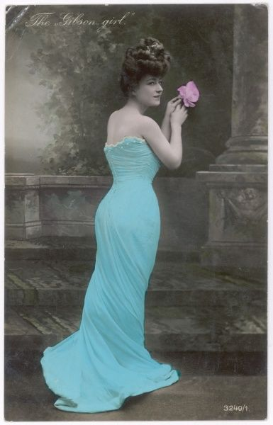 A fashionable Gibson Girl, with hair piled up on her head, long elegant dress and a slim waist