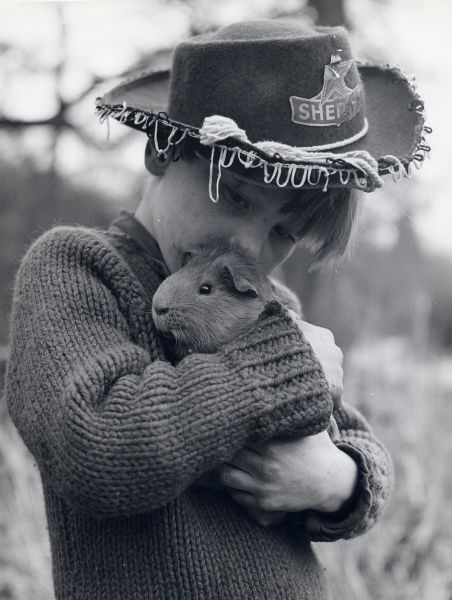 A gipsy boy wearing a Sheriff's hat, cuddling his pet guinea pig