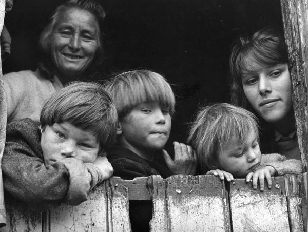 Members of a gipsy family -- two women and three boys -- looking out of the back of their caravan at an encampment in Surrey