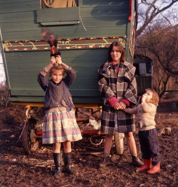 A gipsy family -- mother and two children -- standing outside their caravan in a wooded area