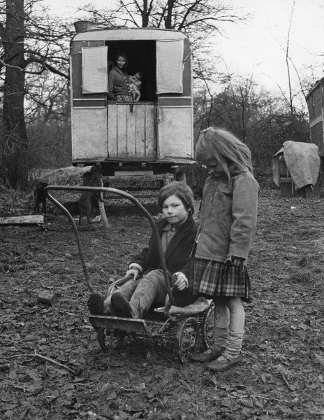 A boy plays on an old pram, with his rather camera-shy sister beside him. A young woman, probably their mother, watches them from a caravan