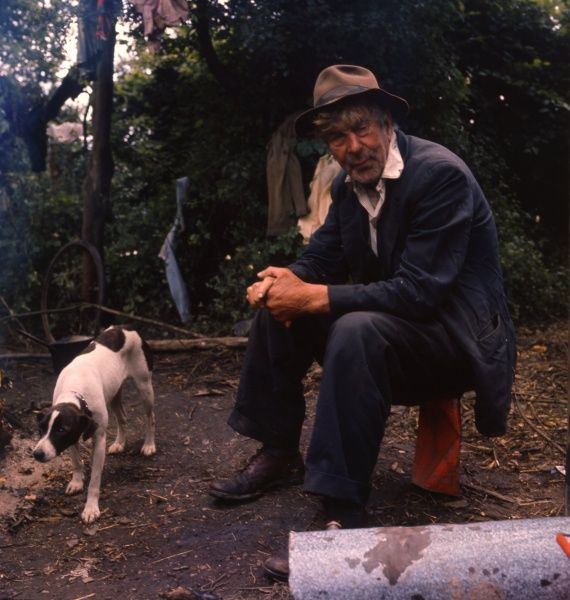 A gipsy man and his pet dog, at an encampment in Surrey. The man sits precariously on a crumpled red tin