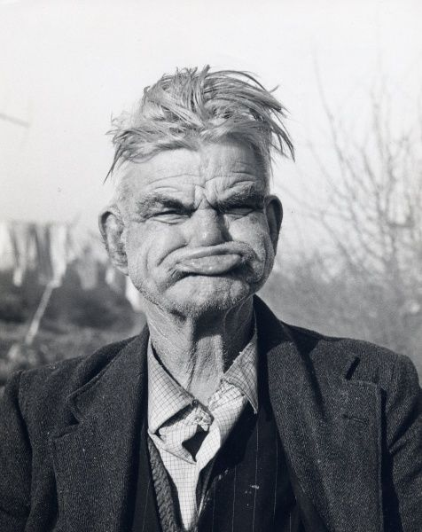A gipsy man pulling a 'gurning face', at an encampment in Lewes, Sussex