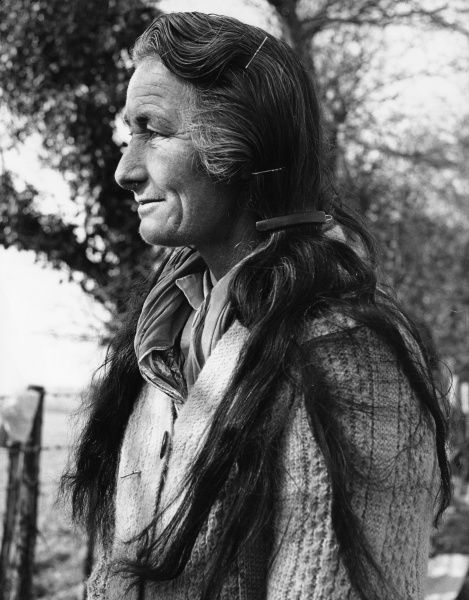 An old gipsy woman in profile, showing her very long hair, pinned back with slides and grips