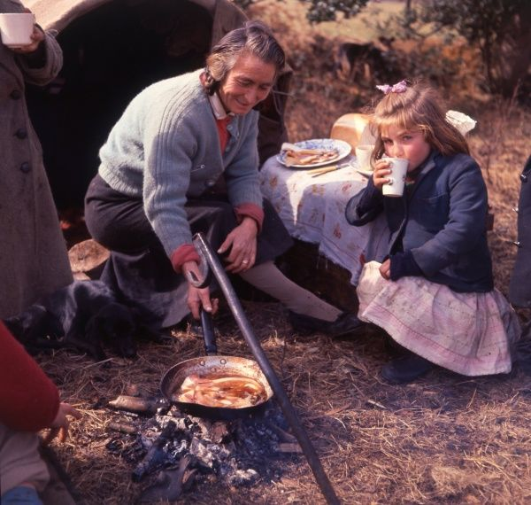 A gipsy woman cooking a fried breakfast in the open air. A little girl crouches nearby, sipping a mug of tea