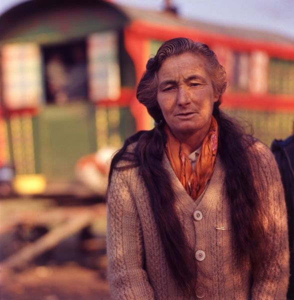 A gipsy woman at an encampment, with long hair, an orange scarf round her neck and a knitted cable-style cardigan. Her caravan can be seen in the background