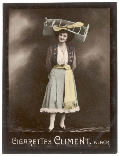A smiling young woman balances on her head a large & unusual aeronautically inspired hat based on a bi-plane. It has an extremely big propellor