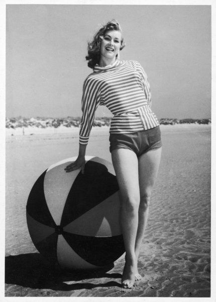 Windswept young lady, wearing shorts & a stripey dolman (batwing) sleeved top with cowl collar leans against a large beach ball to have her photograph taken