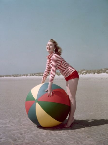 Playful blonde model poses with an enormous beach ball on golden sands wearing a red & white striped cowl neck top & tiny red shorts