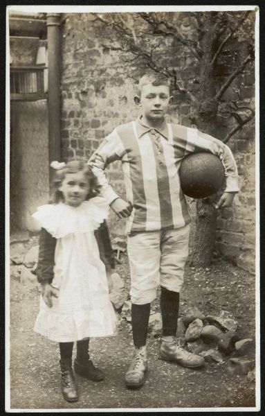 Girl and boy. Boy is wearing a striped football shirt with shorts boots and long socks and is holding a football under his arm