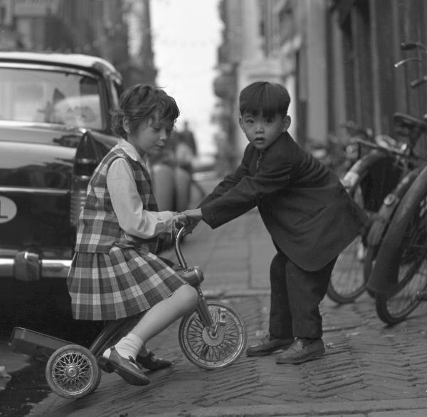 A little girl and boy with a tricycle in the street. The girl is riding the tricycle, while the boy holds the handlebars in front of her